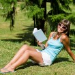 Stock Photo: Happy young woman with book in park