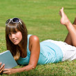 Smiling woman lying down on grass with book — Stock Photo #4692107