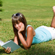 Stock Photo: Smiling young woman lying down on grass with book