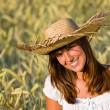 Happy woman with straw hat in corn field — Stock Photo