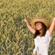 Stock Photo: Happy woman with straw hat in corn field