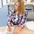 Back to school - female student in classroom — Stock Photo
