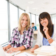 Students with books and laptop in classroom — Stock Photo