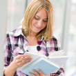 Happy young blond woman holding books — Stock Photo