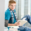 Young man with earbuds and books — Stock Photo