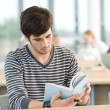 Stock Photo: Young male student read book in classroom