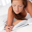 White lounge - Young woman writing notes and lying on bed — Stock Photo #4692748