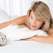 White lounge - Young woman surprised holding alarm clock — Stock Photo