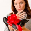Surprised woman holding present shoes — Stock Photo