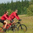 Young couple riding mountain bike in spring meadow — Stock Photo #4693544