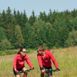 Young couple riding mountain bike in spring meadow — Photo