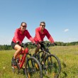Young couple riding mountain bike in spring meadow — Stock Photo #4693551
