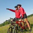 Young couple riding mountain bike in spring meadow — Stock Photo