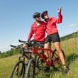 Young couple riding mountain bike in spring meadow — Stock Photo #4693568