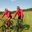 Young couple riding mountain bike in spring meadow — 图库照片