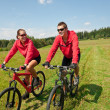 Young couple riding mountain bike in spring meadow — Stock fotografie #4693572