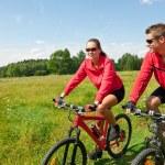 jong koppel paardrijden mountainbike in voorjaar weide — Stockfoto
