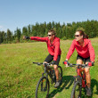 Young couple riding mountain bike in spring meadow — Stock Photo #4693575