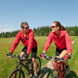 Young couple riding mountain bike in spring meadow — Stock Photo #4693576
