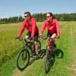 Young couple riding mountain bike in spring meadow — Stock Photo #4693581