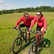Young couple riding mountain bike in spring meadow — Stock Photo #4693584