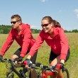Young couple riding mountain bike in spring meadow — Stock Photo #4693588