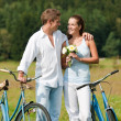 Romantic young couple walking with old bike - Stock Photo