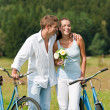 Stock Photo: Romantic young couple walking with old bike