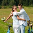 Romantic young couple with old bike in spring nature — Stock Photo #4693607