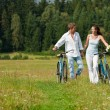Romantic young couple with old bike in spring nature — Stok Fotoğraf #4693619