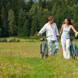 Romantic young couple with old bike in spring nature — Foto de Stock