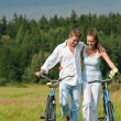 Romantic young couple with old bike in spring nature — Stock Photo #4693621
