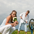 Romantic young couple with old bike in spring nature — Stock Photo