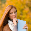 Autumn park - red hair woman with book — Stock Photo