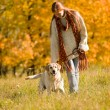 Autumn country - woman walk dog in meadow — Stock Photo