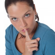 Beautiful young woman with finger on lips — Stock Photo
