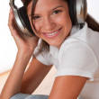 Smiling teenager with headphones listening to music — Foto de Stock