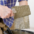 Home improvement - handyman laying tile — Stock Photo