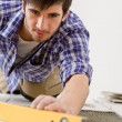 Home tile improvement - handyman with level — Stock Photo