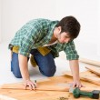 Home improvement - handyman installing wooden floor — Стоковая фотография