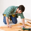 Home improvement - handyman installing wooden floor — Stok fotoğraf