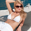 Blond woman sunbathing on luxury yacht with bikini — Stock Photo