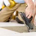 Home improvement, renovation - handyman laying tile — Stock Photo #4695143