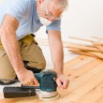 Home improvement - handyman sanding wooden floor — Stock Photo