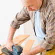 Home improvement - handyman sanding wooden floor — Stock Photo