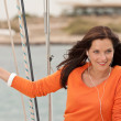 Attractive woman standing on sailing boat with headphones - Photo