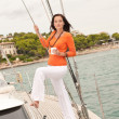 Young woman standing on sailing boat with cup of coffee - Stock Photo