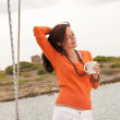 Young woman standing on sailing boat with cup of coffee — Stock Photo