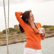 Young woman standing on sailing boat with cup of coffee — Stock Photo #4695258