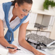 Smiling female architect watching plans — Stock Photo